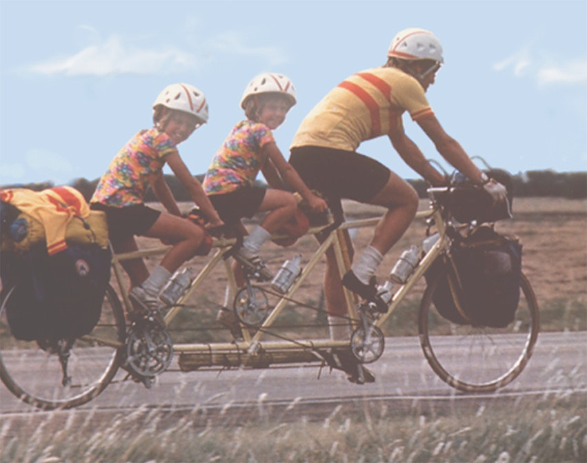 <p>Bill Bliss riding with his daughters Heather and Shannon in 1976 on a special three-seater bicycle he built. </p>