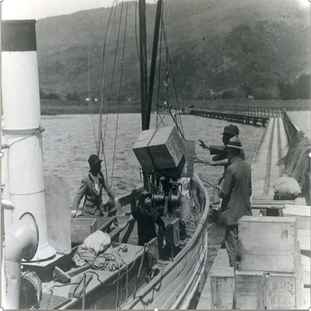 <p>SS Tongariro moored at the Tokaanu Wharf unloading 'Big Tree' benzene. The lake near Tokaanu is shallow so the wharf was extended to ease the transfer of both goods and passengers. The 260 metre wharf at Tokaanu is still in existence. It is one of the oldest wharves in New Zealand.</p>