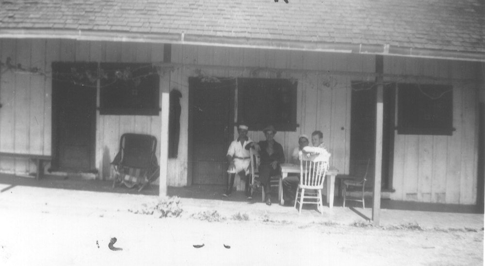 <p>Bunkhouse. Workers relaxing on the northern side of the original bunkhouse, 1940.</p>
