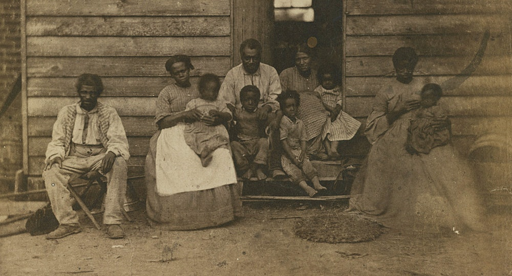 <p>Photograph shows African American slave family or families posed in front of wooden house, on the plantation of Dr. William F. Gaines, Hanover County, Virginia.</p>