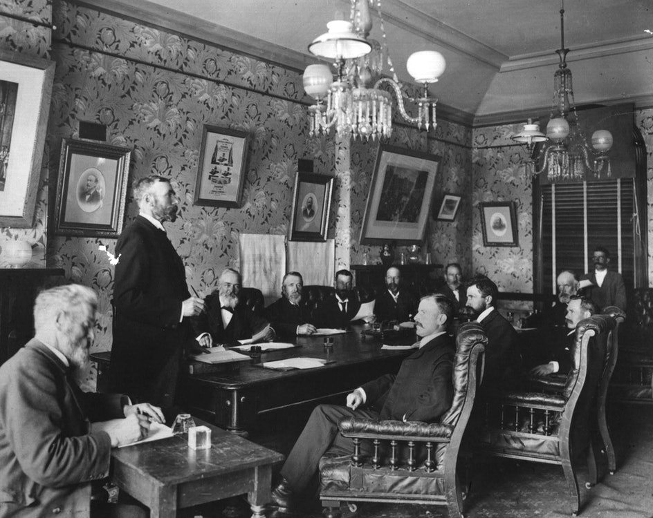 <p>James Craigie (standing at left) leading a Timaru Borough Council meeting in 1902</p>