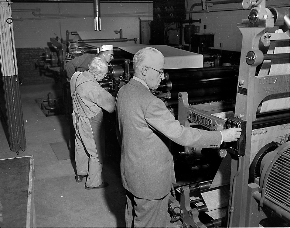 <p>Brattleboro Reformer publisher Howard C. Rice presses the button to start a test run on<br>a new press prior to the regular run of the daily newspaper in 1954. At left Paul Hescock,assistant pressman and veteran pressman Harold Jennings, are responsible for getting out The Reformer six days a week. (Oct. 1, 1954, Brattleboro Reformer Harold Asbury) - photo courtesy of the Brattleboro Historical Society</p>