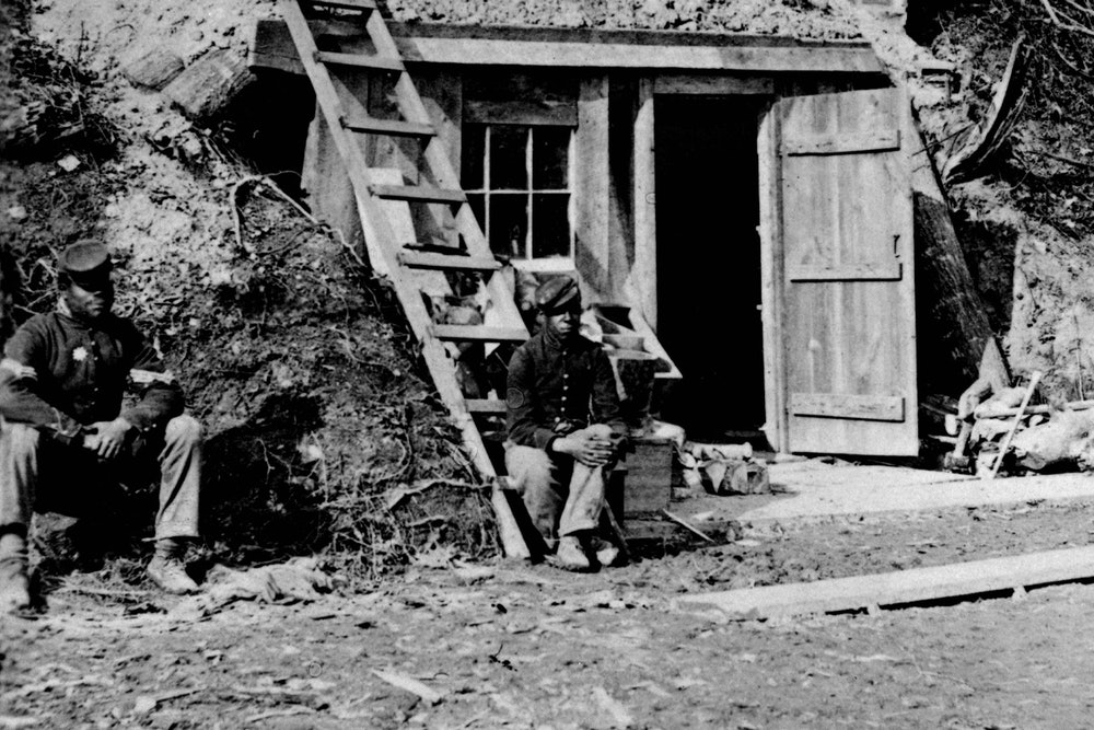 <p>In this photograph taken in November 1864, two African American soldiers sit in front of small building in bottom of cliff, near Dutch Gap Canal.</p>