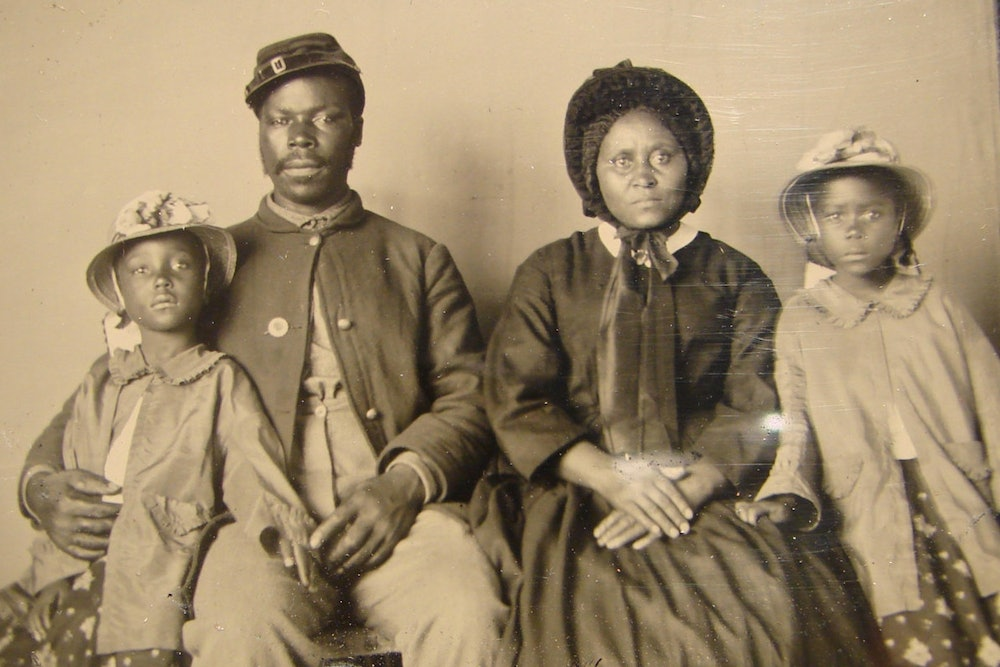 <p>Unidentified African American soldier in Union uniform with wife and two daughters</p>