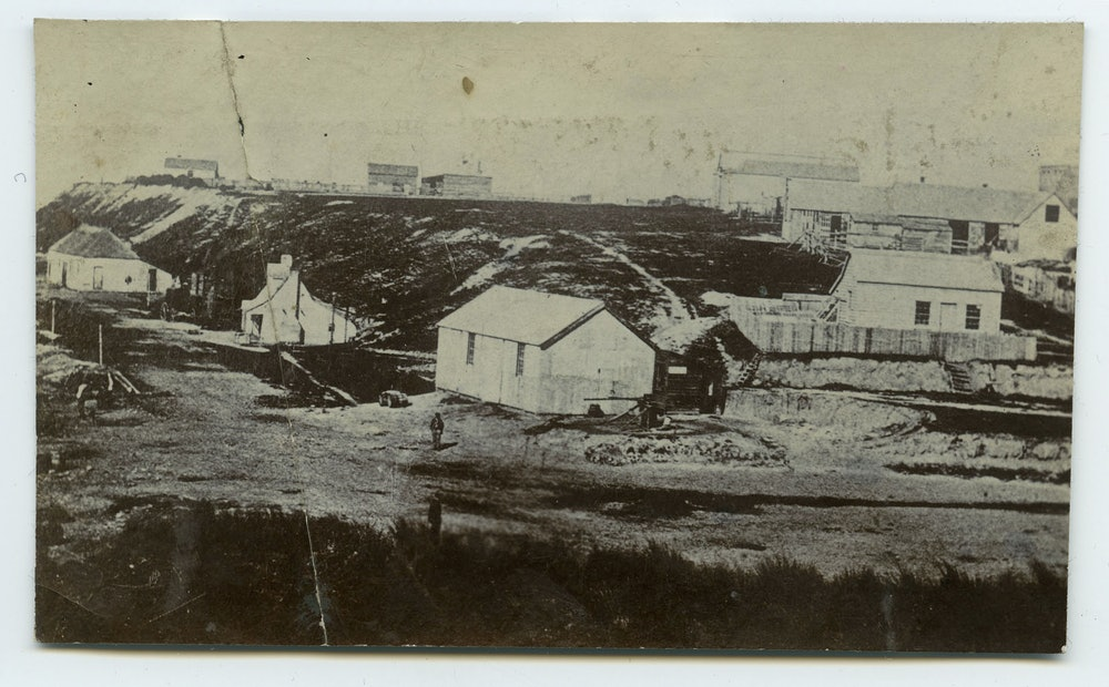 <p>The foot of George Street, Timaru, circa 1868.  The building in the centre is a landing service building (either the Timaru Landing and Shipping Company or the George Street Landing Service), while Rhodes' original cottage is to the left.</p>